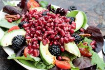 31703452 - a healthy salad with pomegranate, avocado, tomatoes, almonds and argula lettuce over a rustic background.
