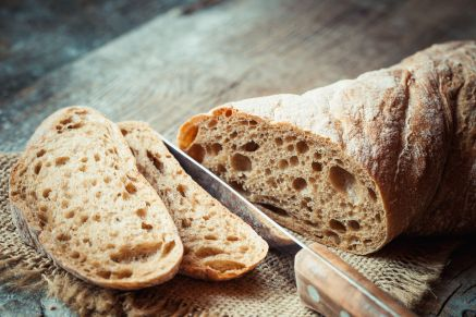 49984315 - fresh bread slice and cutting knife on rustic table